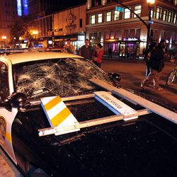 A BART police vehicle is vandalized during a protest after George Zimmerman was found not guilty in the 2012 shooting death of teenager Trayvon Martin, early Sunday, July 14, 2013, in Oakland, Calif. Protesters angered by the acquittal Zimmerman held largely peaceful demonstrations in three California cities, but broke windows and started small street fires Oakland, police said. (AP Photo/Bay Area News Group, Anda Chu)