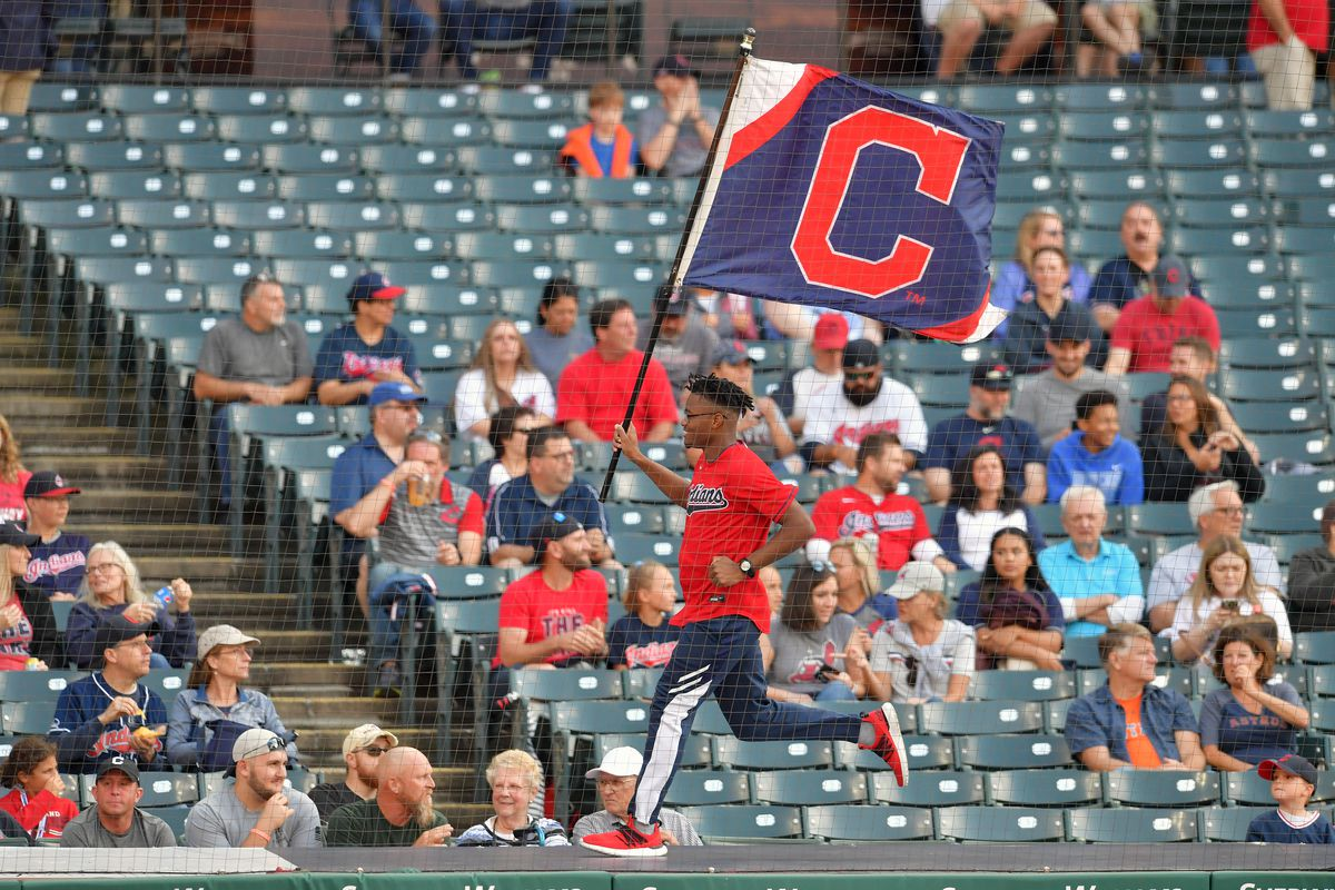 A Cleveland Indians employee runs with a flag displaying the block C logo prior to the game against the Houston Astros at Progressive Field on July 02, 2021 in Cleveland, Ohio.