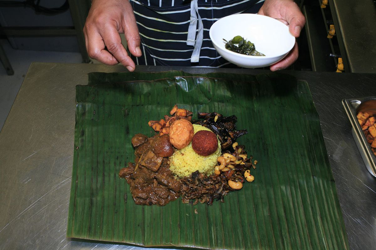 Lamprais, fully assembled on its banana leaf, being garnished with chilli and curry leaves