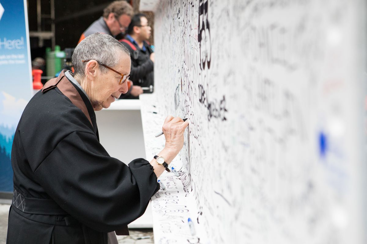 Zen priest Jisan Tova Green of the SF Zen Center signs the final beam.