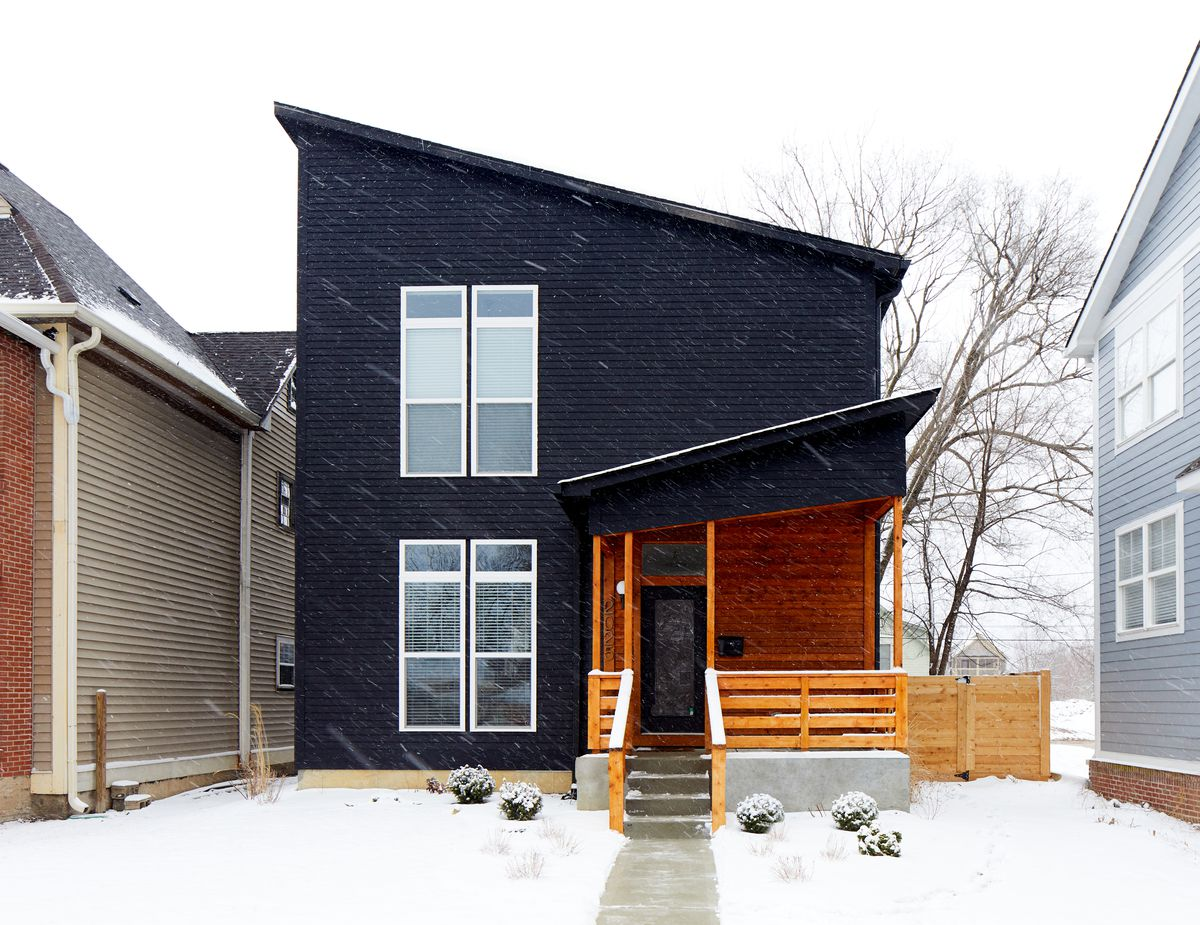 The exterior of a house which is painted black. The doorway area and porch are made of orange toned wood. There is snow on the ground in front of the house.