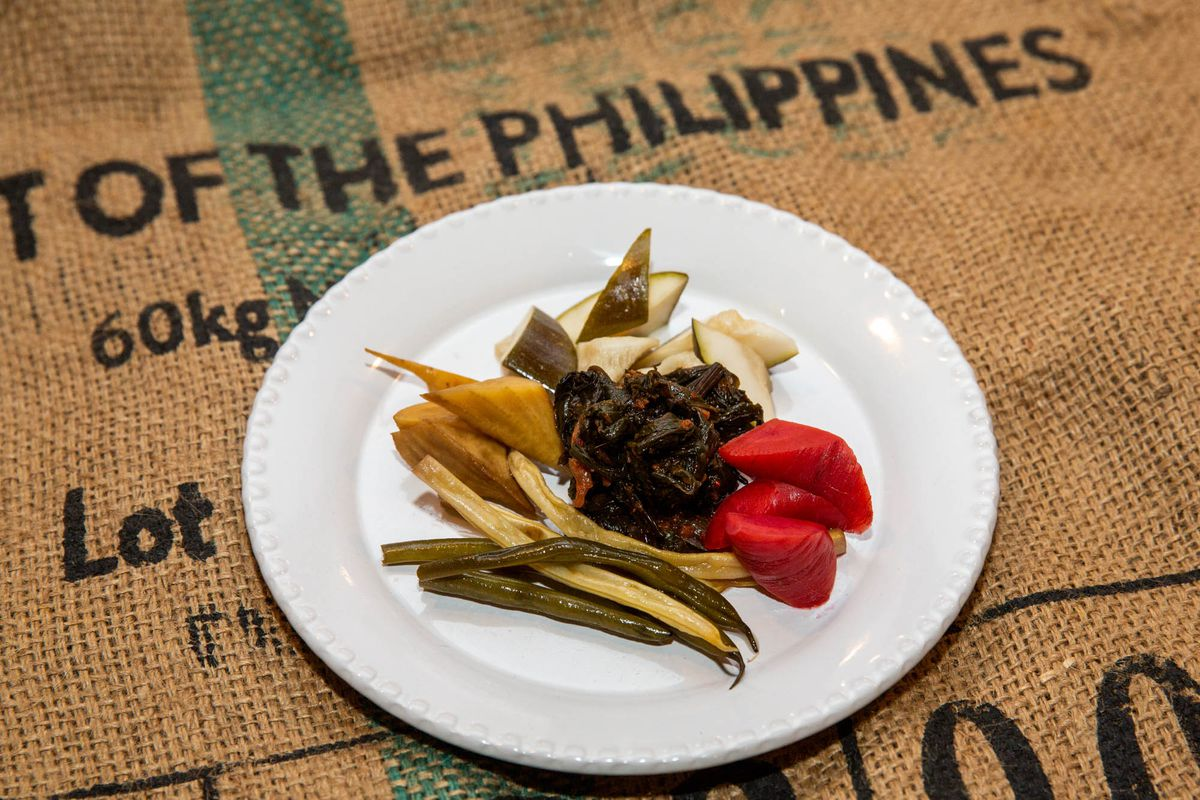 A plate of pickled vegetables on a plate against a brown burlap sack.