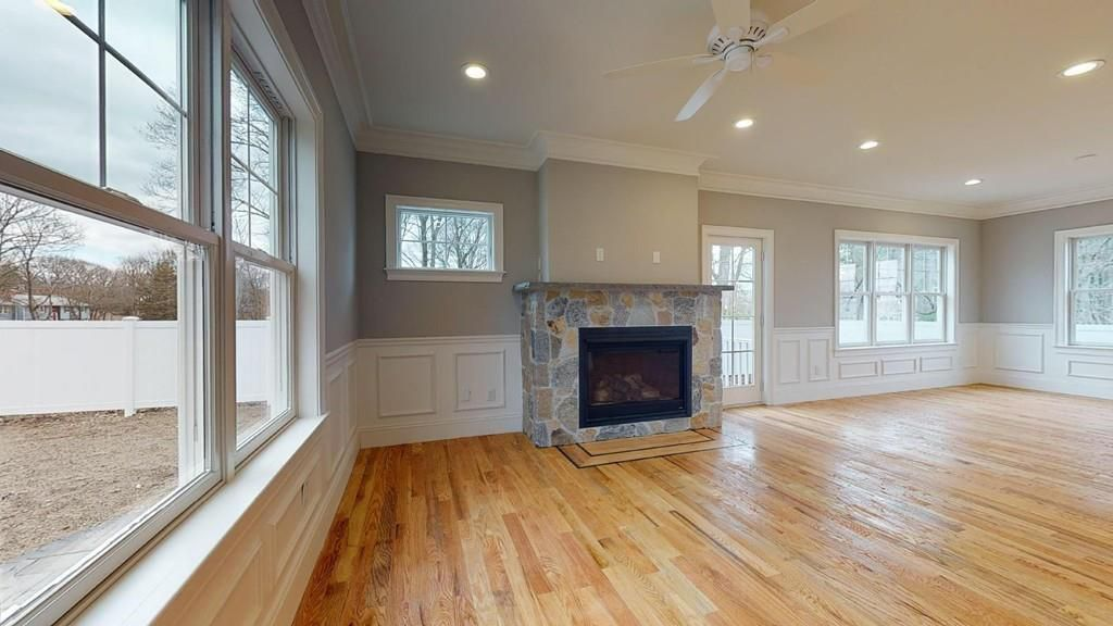 An empty, spacious living room with a stone fireplace.