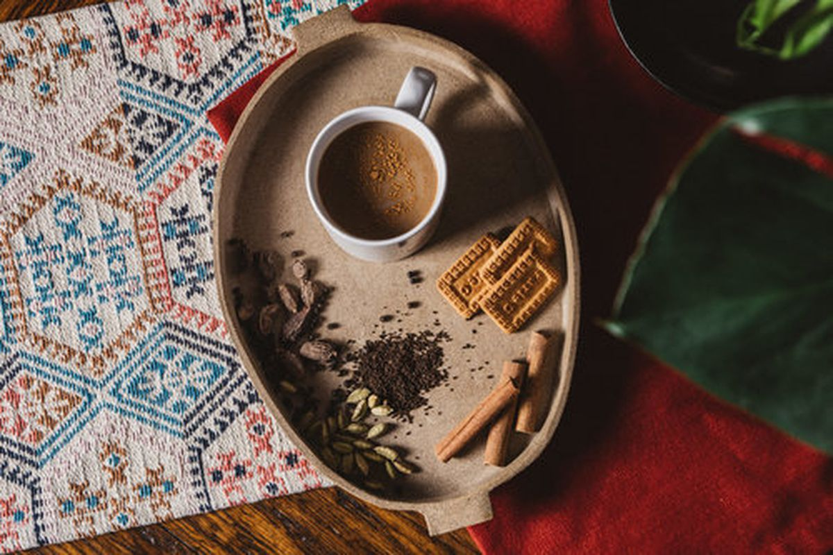 A brown tray with a cup of masala chai, with cinnamon sticks and crackers and spices