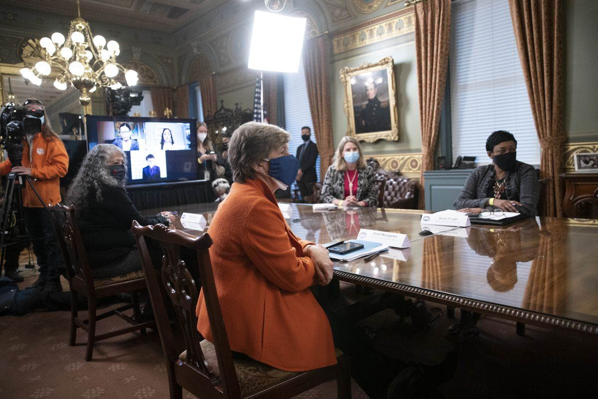 Four women sit around a table during a meeting to commemorate Women's History Month. AFT President Randi Weingarten is on the left side of the table wearing an orange jacket and blue mask. There is a projection on a television in the background and a member of a film crew.