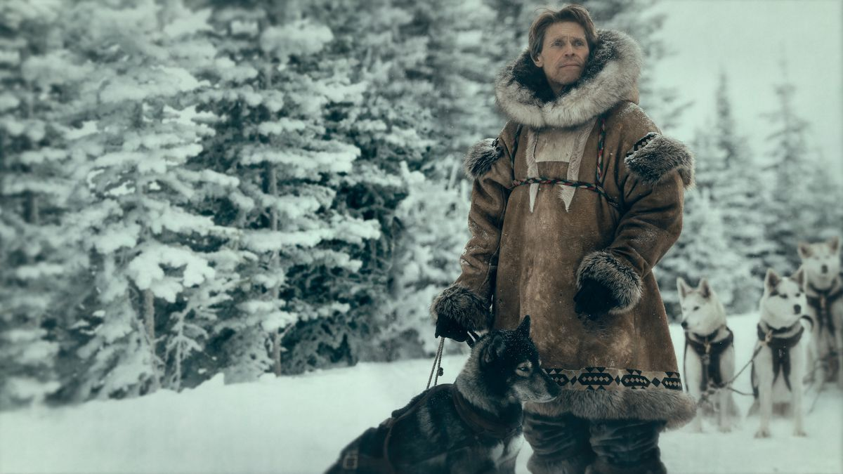 Dafoe in a giant coat, surrounded by dogs.