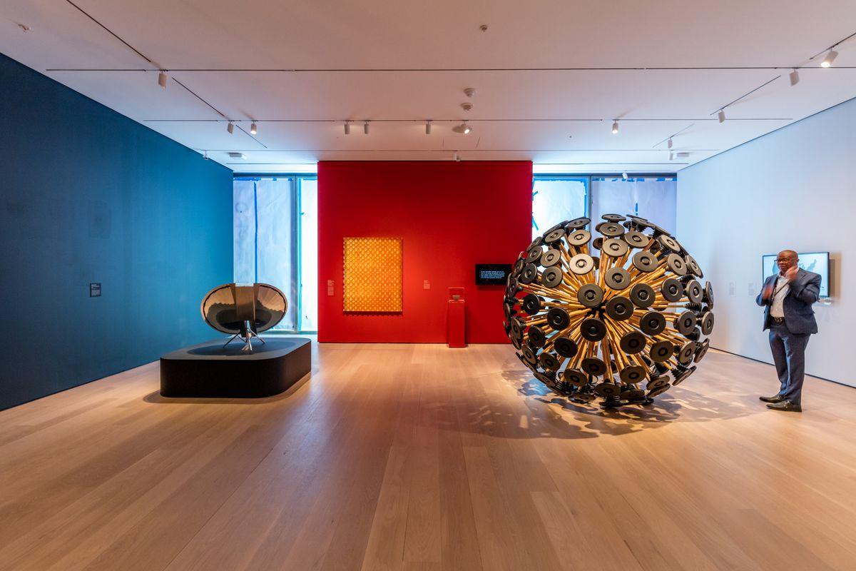 A gallery space with black and red walls and a round sculptural piece.