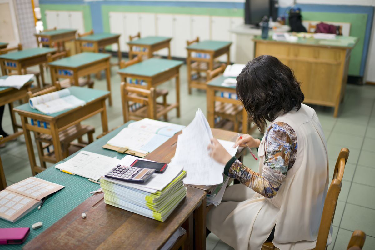 A teacher grades papers in a classroom.