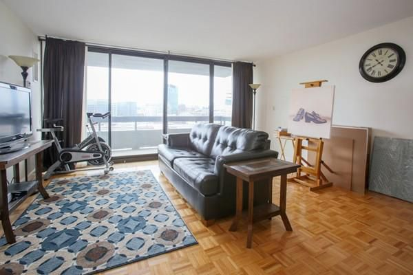 A studio apartment with a couch facing the TV and sliding glass doors just beyond leading to a balcony,