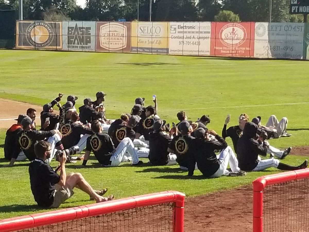 Volcanoes players watch the eclipse and take photos while seated together on the field while it's still light outside