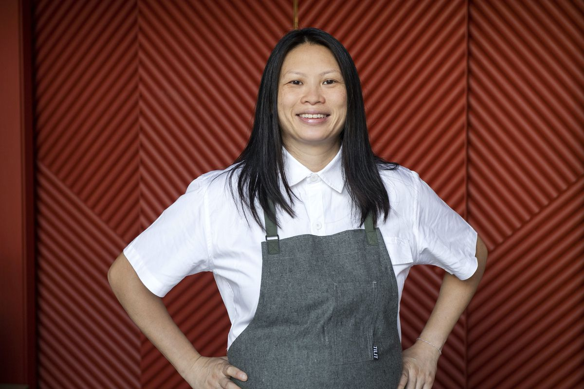A female chef in a white dress shirt and grey apron standing in front of a red background.