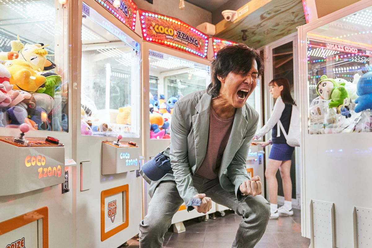 A man in a gray jacket and pants bends over screaming in an arcade in Squid Game