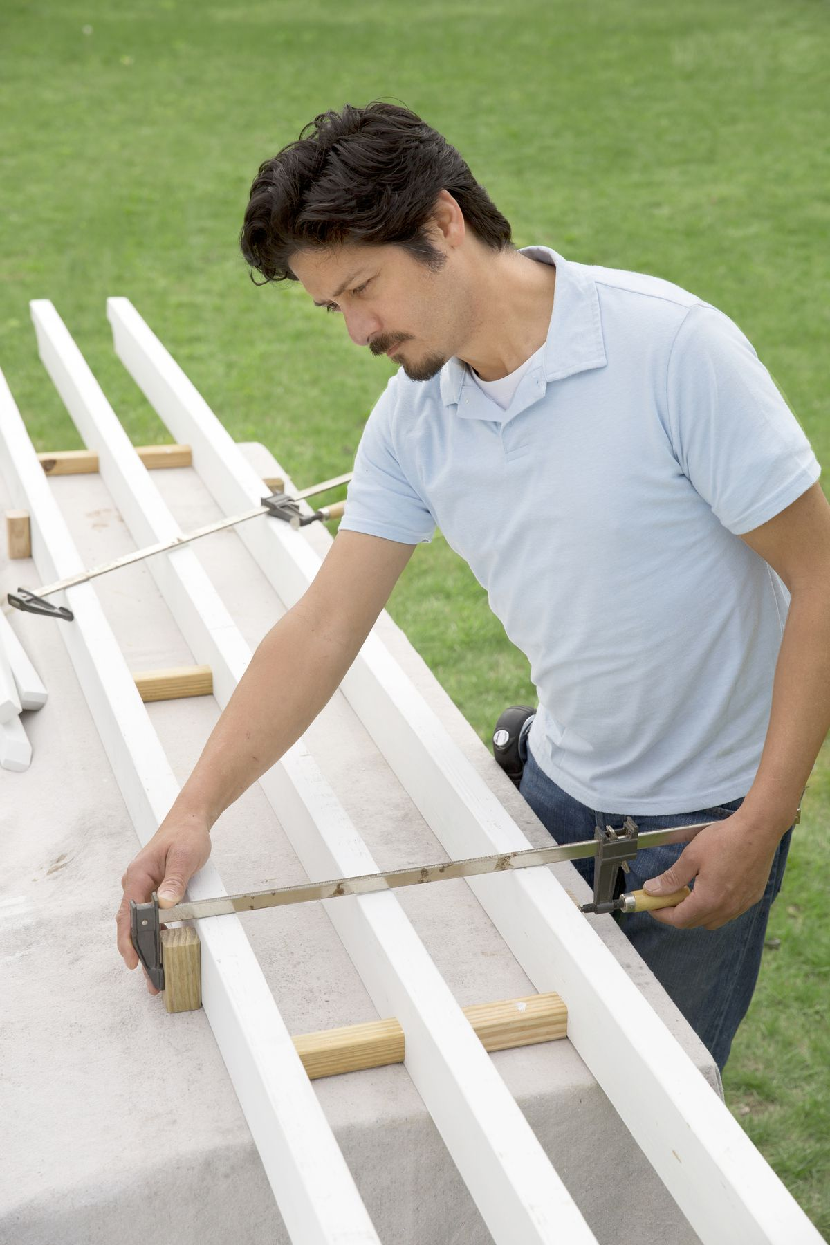 Man Clamps Assembly Together Of Garage Pergola