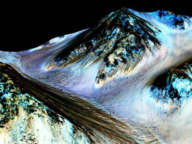According to NASA: Dark, narrow streaks on Martian slopes such as these at Hale Crater are inferred to be formed by seasonal flow of water on contemporary Mars.