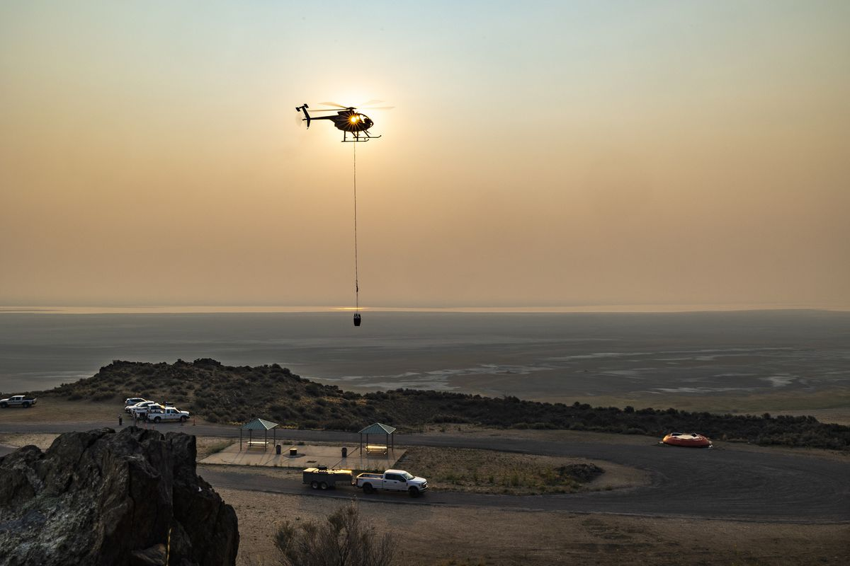 A helicopter flies in to dip water as Utah Division of Wildlife biologists partner with Utah State Parks to fill six of the remote guzzlers at Antelope Island State Park in an effort to provide water to the island's bighorn sheep on Monday, Aug. 16, 2021. Guzzlers are large devices that catch and store water from snow and rain. They provide drinking water for wildlife and are especially important during hot, dry summers and drought years. However, due to the extreme drought this year, some of these guzzlers have run out of water in different areas across the state.