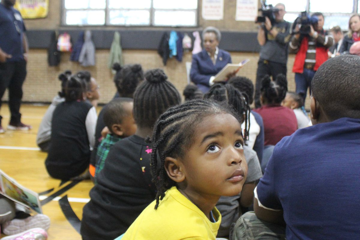 A student spending Wednesday morning at Kennicott Park in Kenwood glances up at media cameras as Mayor Lori Lightfoot reads a book aloud to a group of children during the 10th day of the teachers strike.