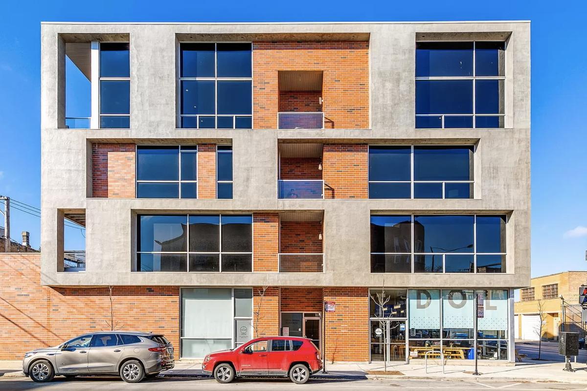 A brick and concrete condo building with large square windows.