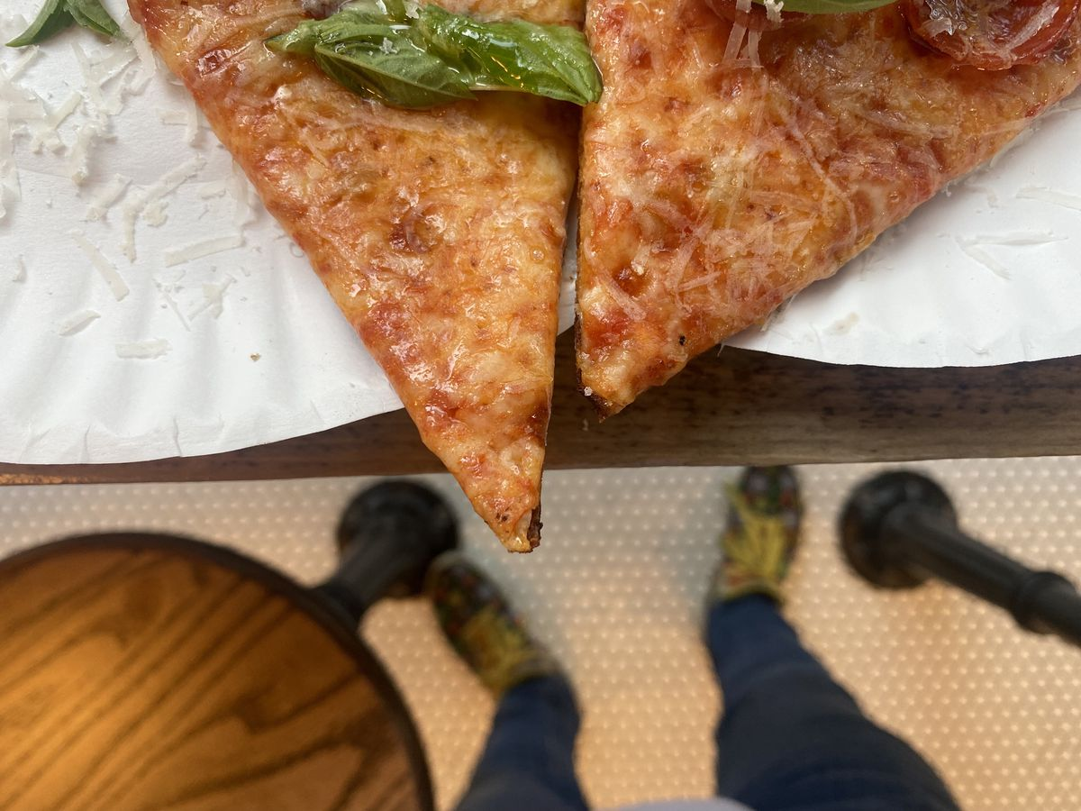 The tips of two slices, margherita on the left, pepperoni on the right, hang just over the edges of white paper plates in this overhead shot; a single leaf of basil sits over the margherita slice