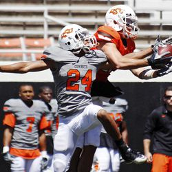 Oklahoma State wide receiver Charlie Moore, right, catches a pass in front of defender Miketavius Jones, left, during a spring NCAA college football game in Stillwater, Okla., Saturday, April 21, 2012.