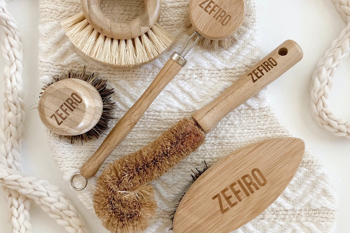 Kitchen brushes with wooden handles are displayed on a white towel.