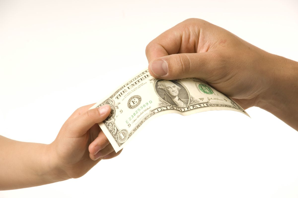 close-up adult hand taking dollar bill from child's hand