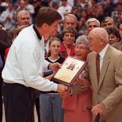 Gifford Nielsen presents award to former BYU basketball coach Stan Watts.  Stan's wife Emily is in the center of the photo. photo by ravell call jan. 31, 1998
