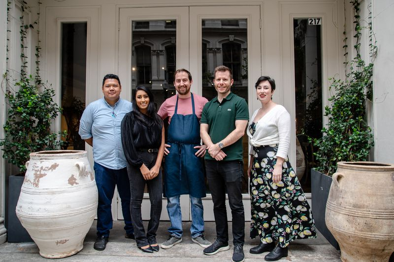 Rockrose staff including chef Brian Doyle (center) and proprietor/GM Nick Asprodites, right, and bar manager Jennifer Hussey, far right, stands outside of the restaurant