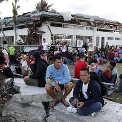 People wait in line at the airport, seeking passage on military transport planes to leave Tacloban, Tuesday, Nov. 19, 2013, following Typhoon Haiyan in the Philippines.