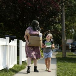 Faith Olague and her sister, Kylee, carry food home after their neighbor, Jerry Dolejs, visited the Utah Food Bank mobile pantry at The Church of Jesus Christ of Latter-day Saints' Cannon Stake Center in Salt Lake City on Wednesday, Sept. 1, 2021. Dolejs keeps a few items for himself and gives the majority of the food to the Olague-Babwright family.