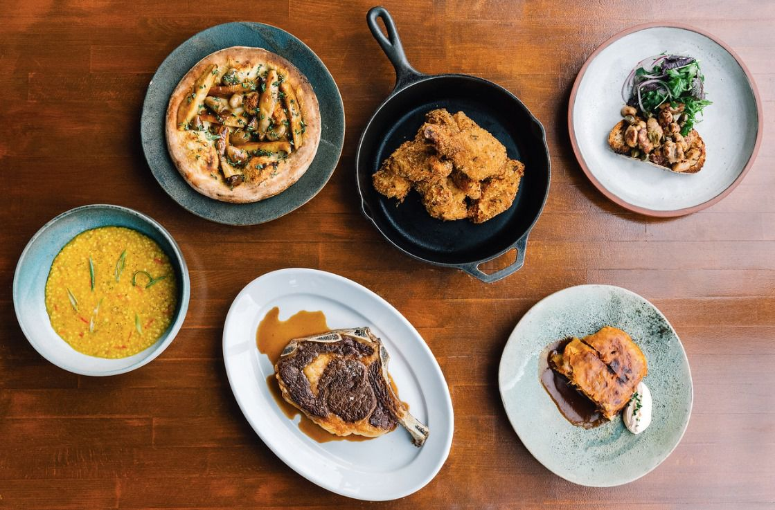 A wood table topped with various dishes, including steak, fried chicken, and risotto