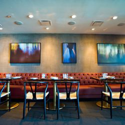 Impressionist paintings sit above rust-colored leather banquettes