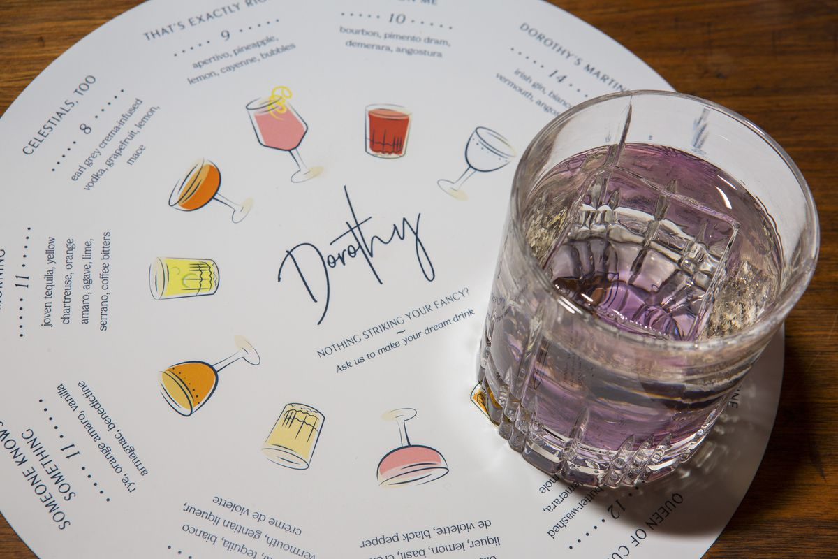 A round rink menu with illustrations, and a purple-ish drink on the right.