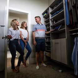 """Brooke Shaw listens with Savanna Shaw and Mat Shaw to a recording of their cover of the song """"Shallow"""" inside a closet in their family's home on Thursday, May 14, 2020. The father-daughter duets went viral on YouTube as they shared their passion for music amid the COVID-19 pandemic. """"The one thing more contagious than a virus is hope and so we're just doing our small part in the world to spread some hope,"""" Mat Shaw said."""