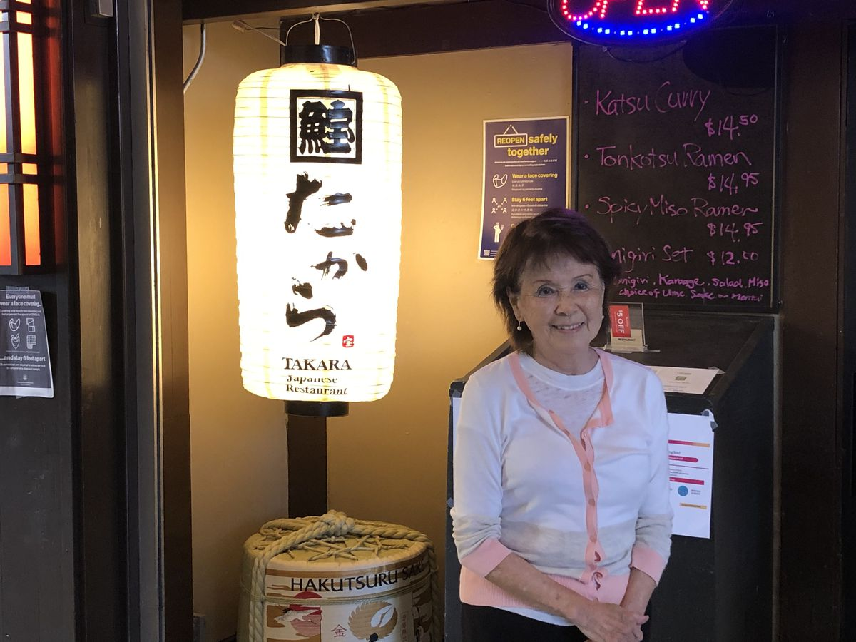 Takara owner Lena Turner stands next to the lantern sign in front of her restaurant Takara