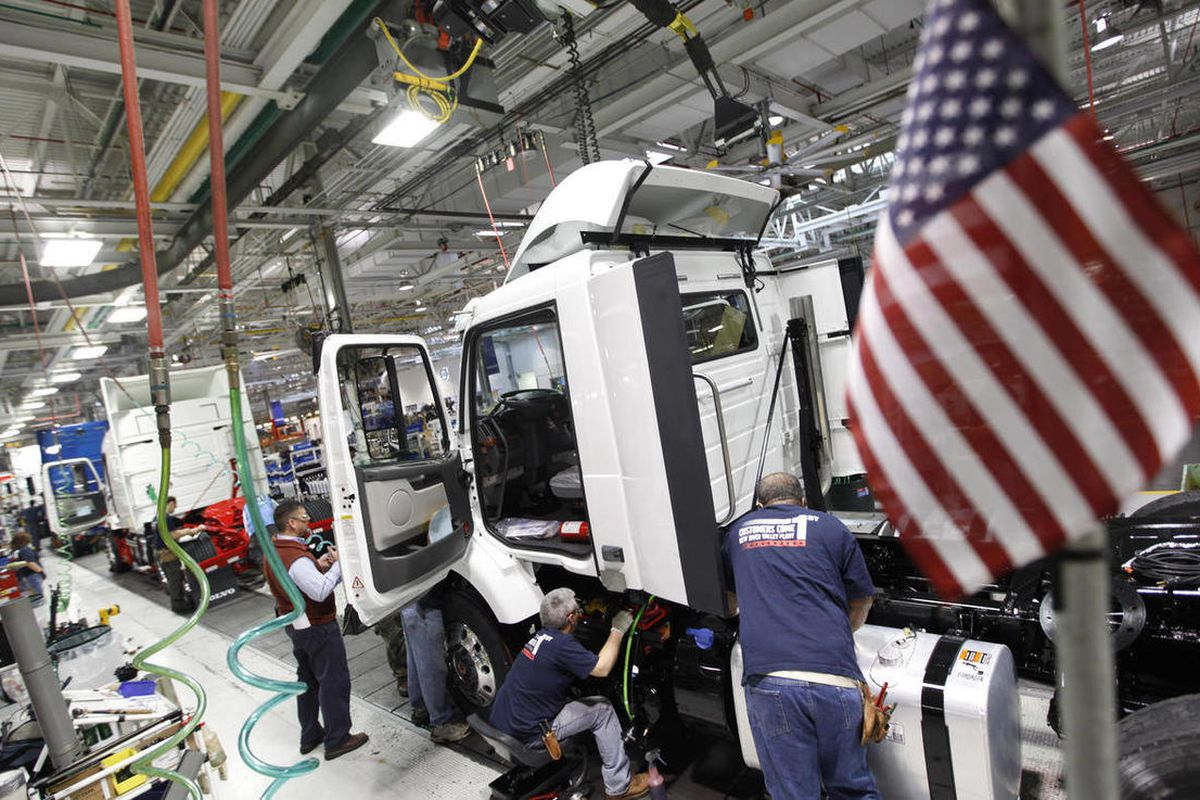 In a Jan. 6, 2011 photo workers install parts on a truck on the Volvo truck assembly line at the Volvo plant in Dublin, Va.   The government on Friday will make its first estimate of growth for the January-March quarter.