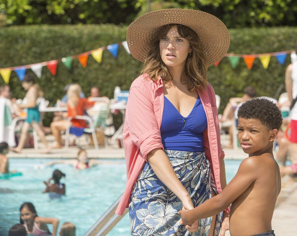 A woman and a small child stand in front of a swimming pool with children swimming. There are colorful flags draped over the pool.