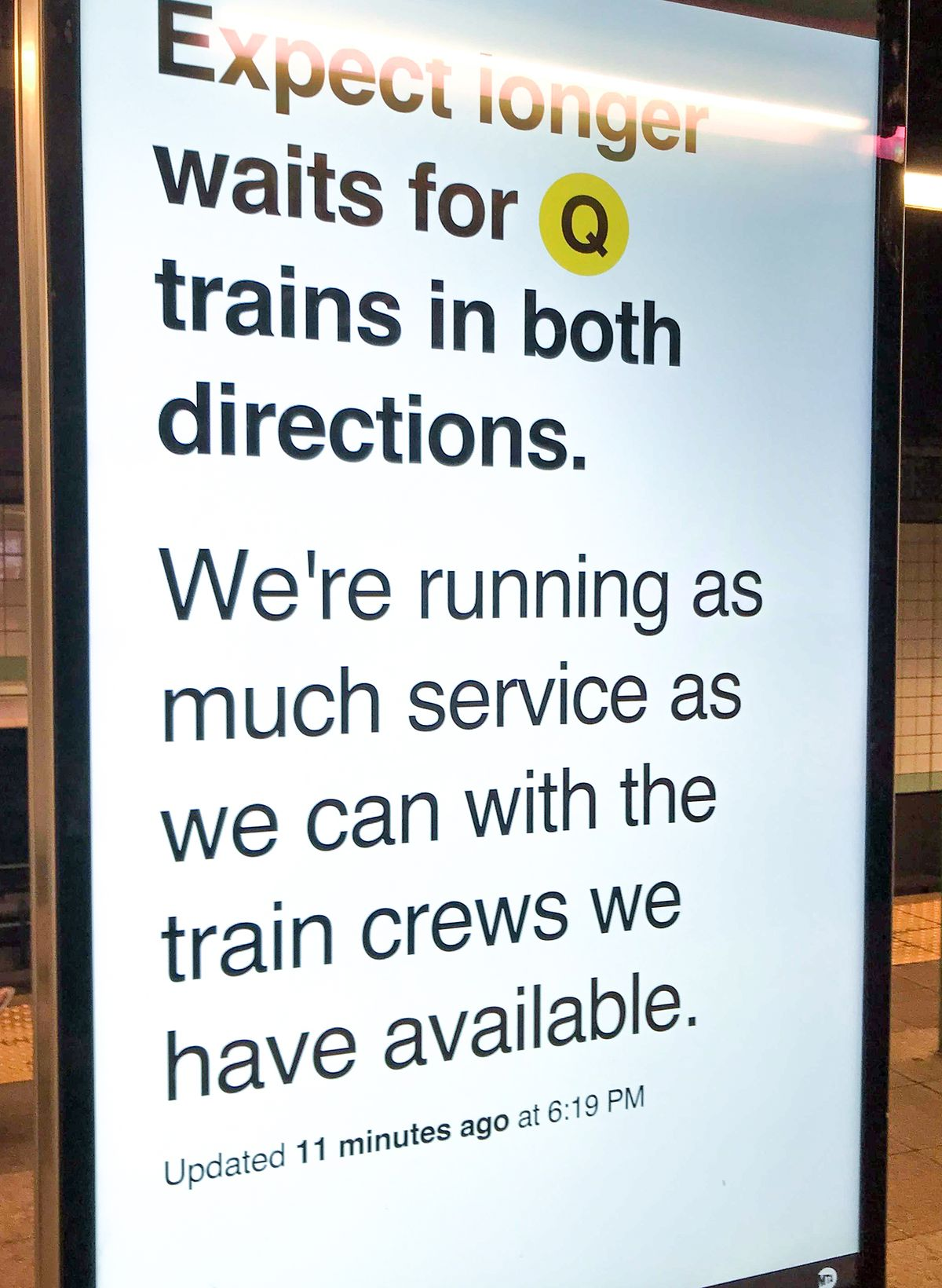 A sign in a station on the Q line on May 23, 2021, blames delays on crew shortages.