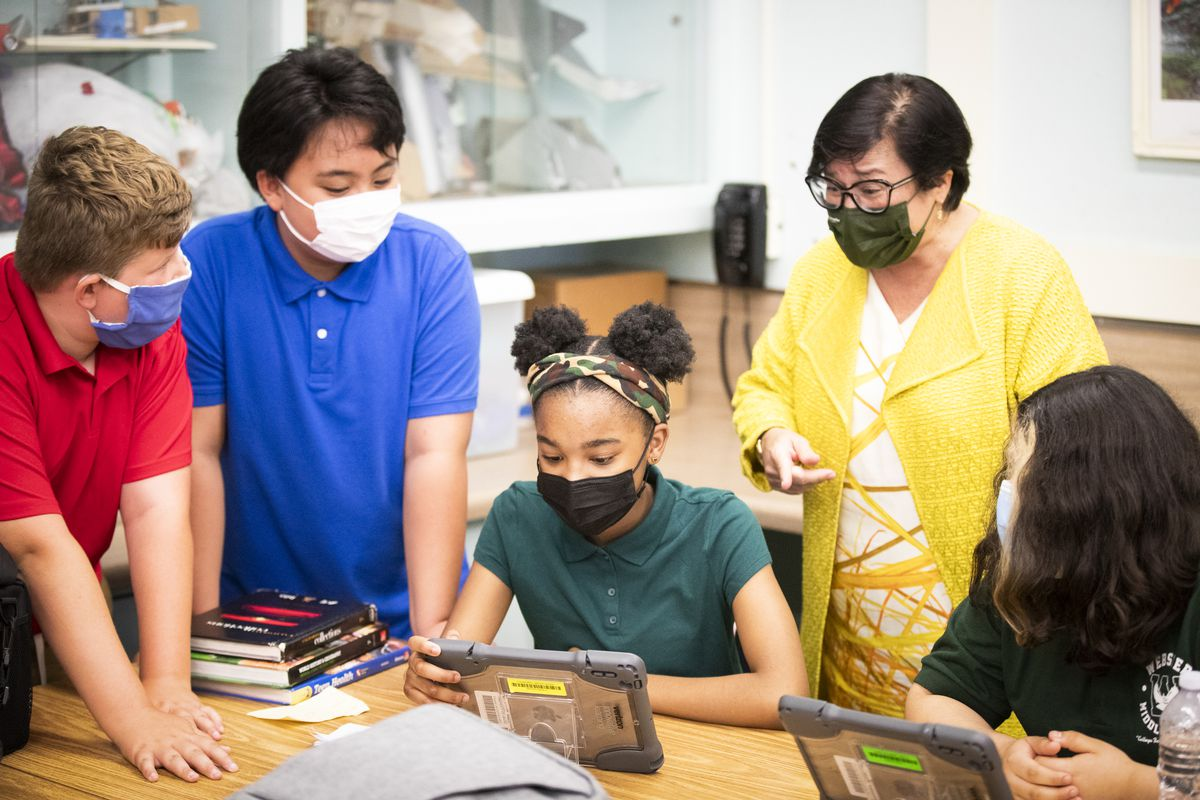 Middle-school students wearing masks gather around a desk and  get instructions from their teacher.