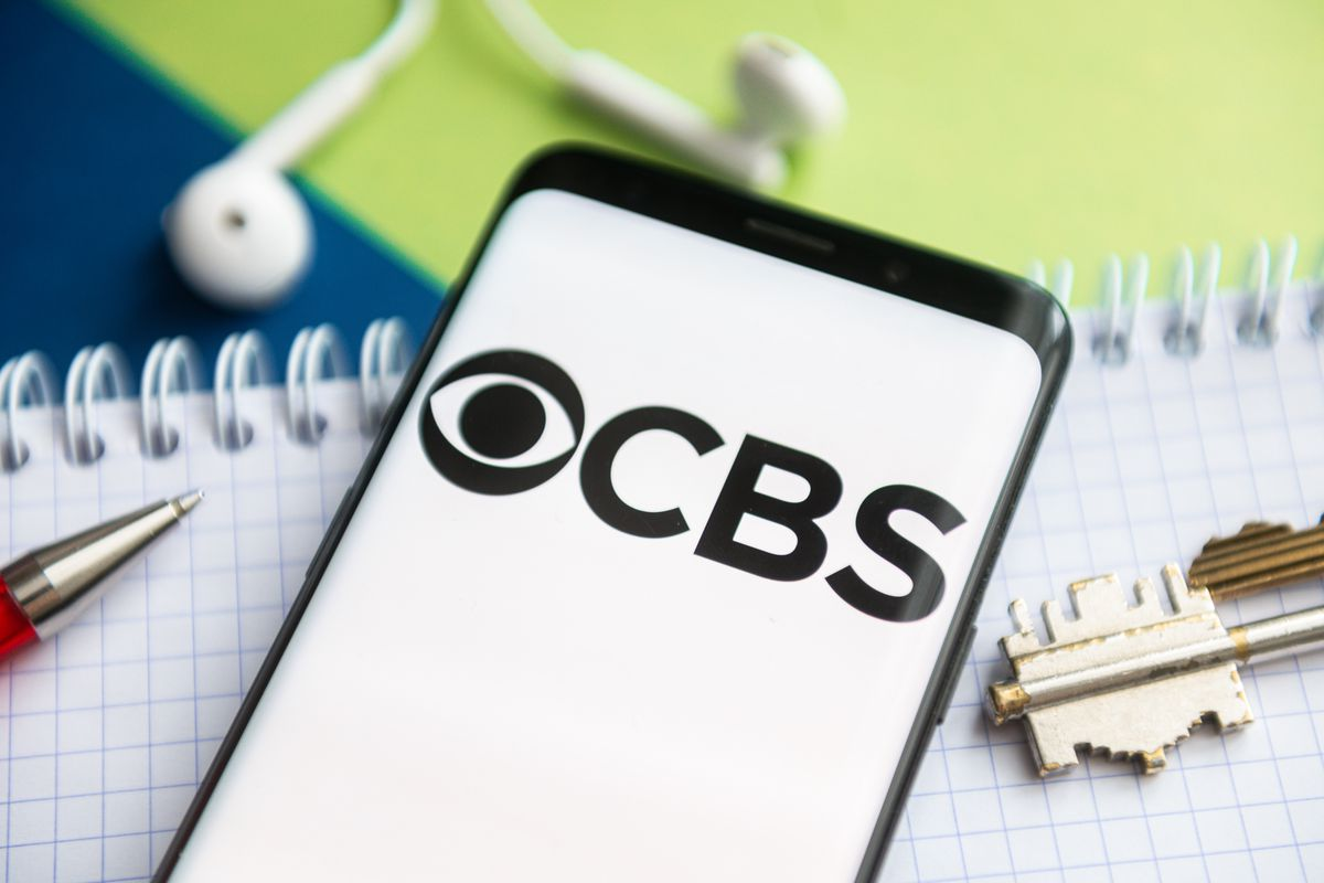 In this photo illustration, a CBS logo seen displayed on a...