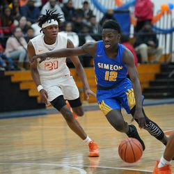 Simeon's Ahamad Bynum (12) blows by Young's CJ Stewart (21), Wednesday 02-13-19. Worsom Robinson/For the Sun-Times.