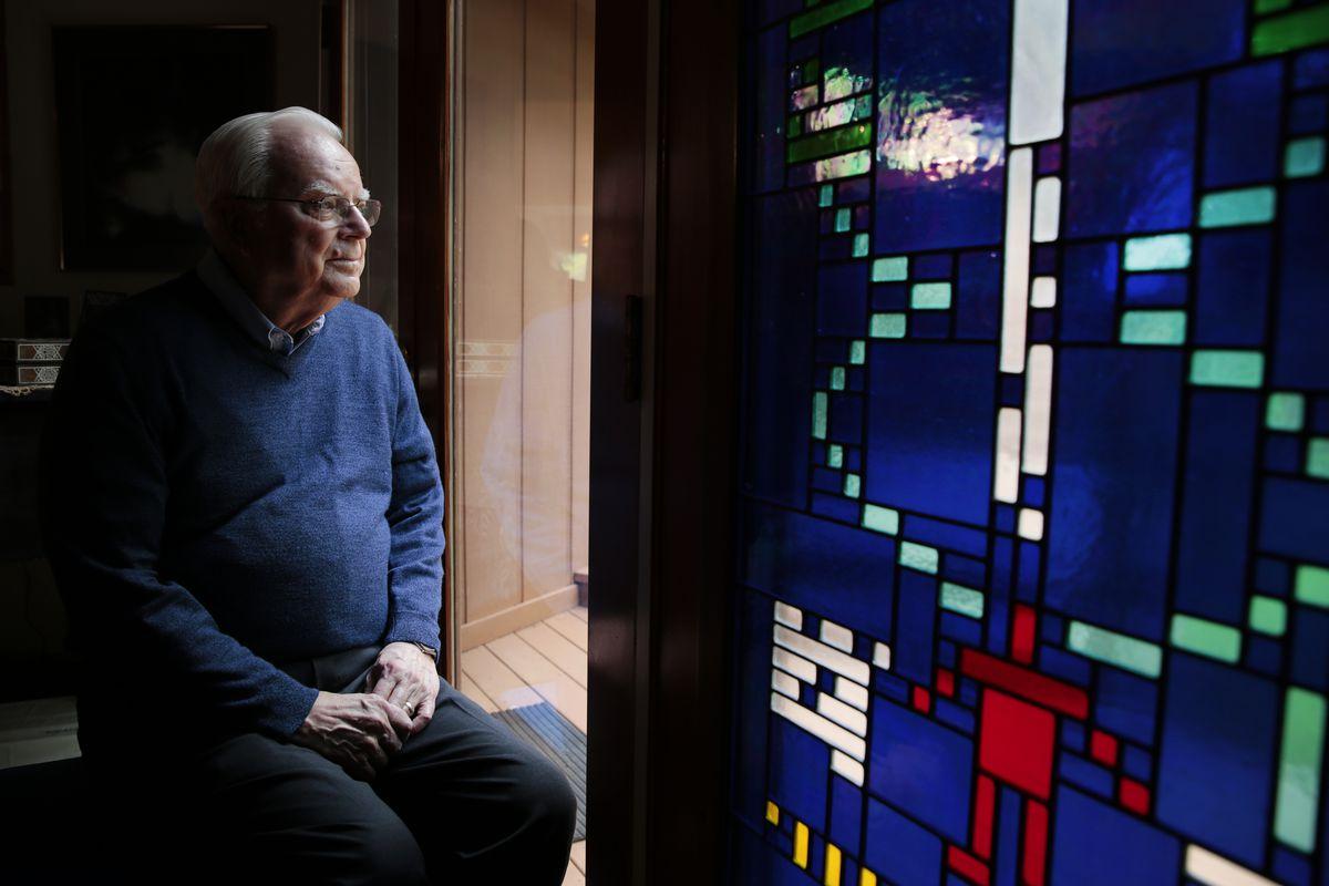 Frank Drake est assis à côté d'un vitrail montrant le message d'Arecibo chez lui en Californie.