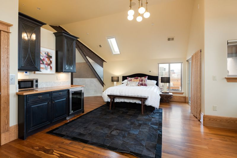 A bedroom with a white bed, black rug, wooden floors, vaulted ceilings and a kitchenette.