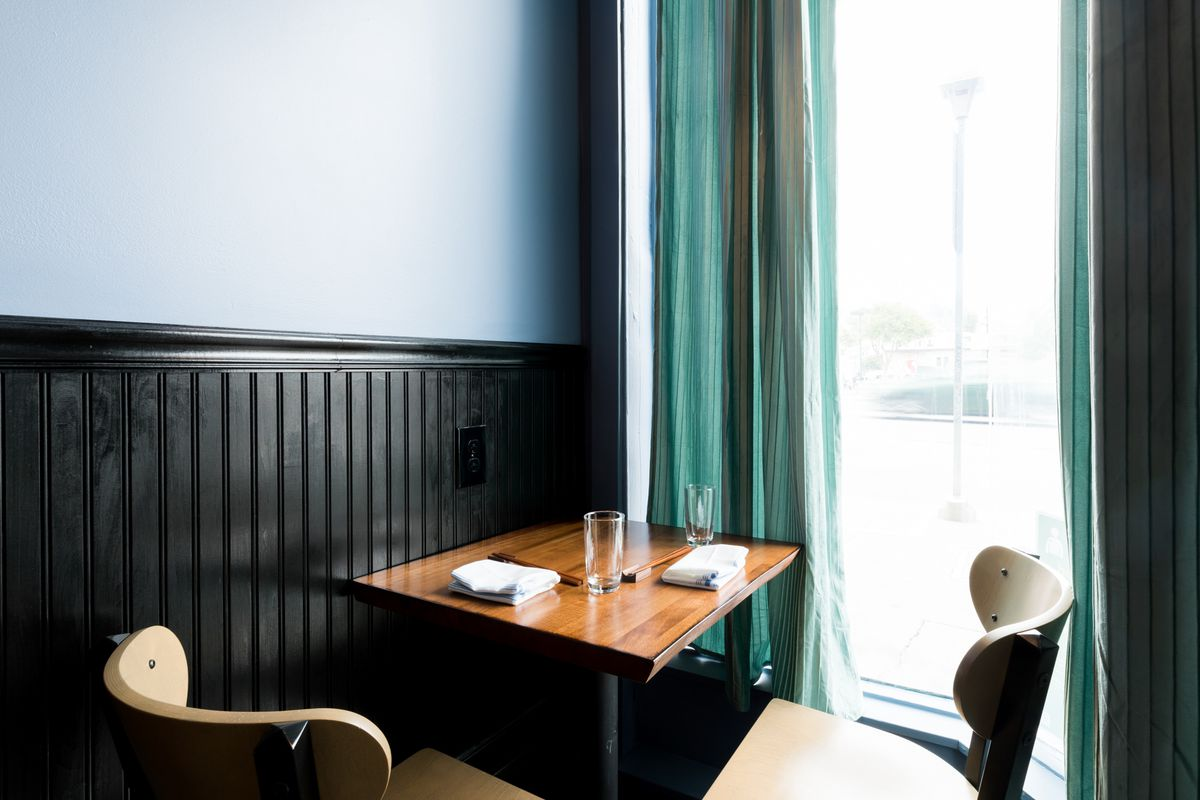 A front table for two at Chisai Sushi Club. The window is hung with turquoise curtains.