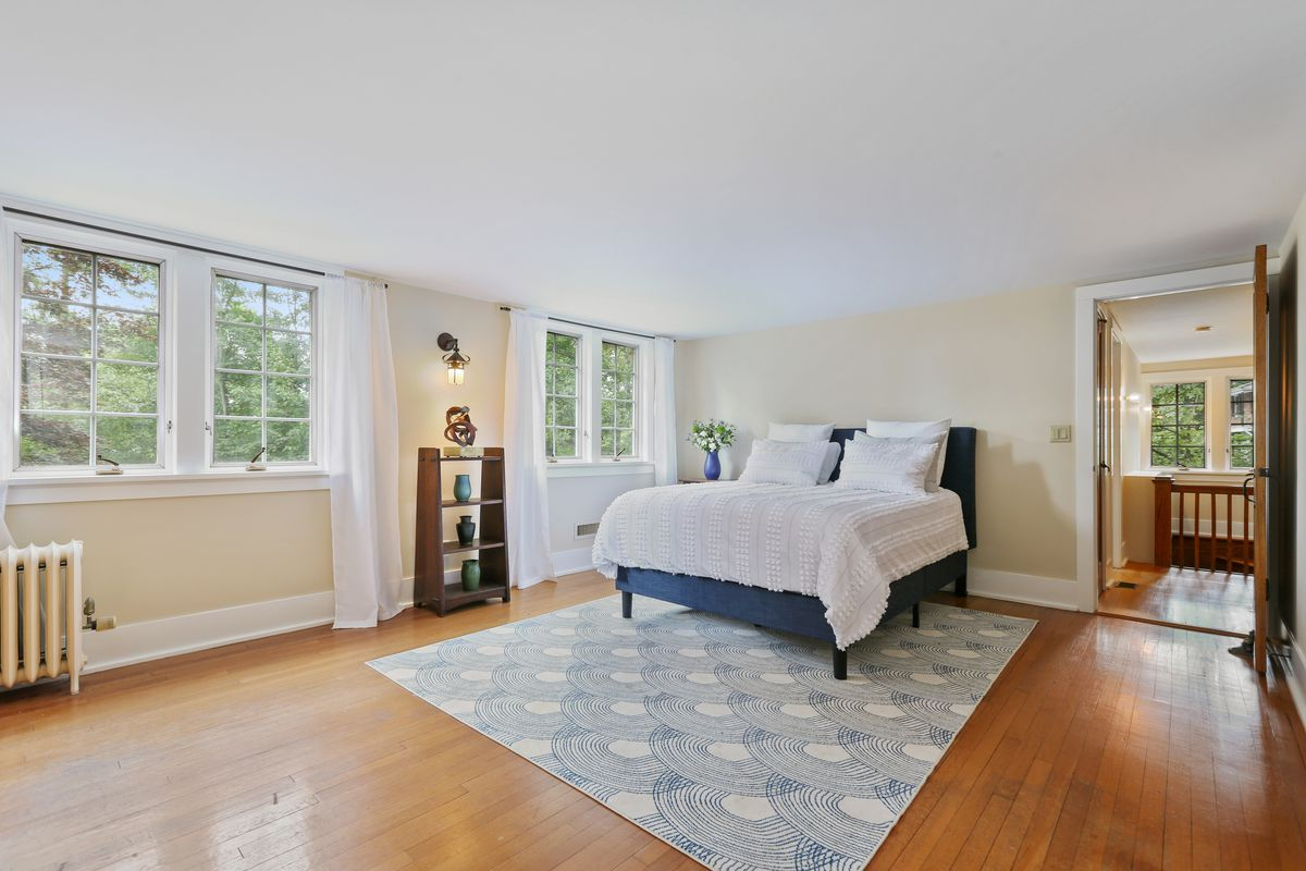 A bright bedroom has a white bed, blue rug, and big windows.