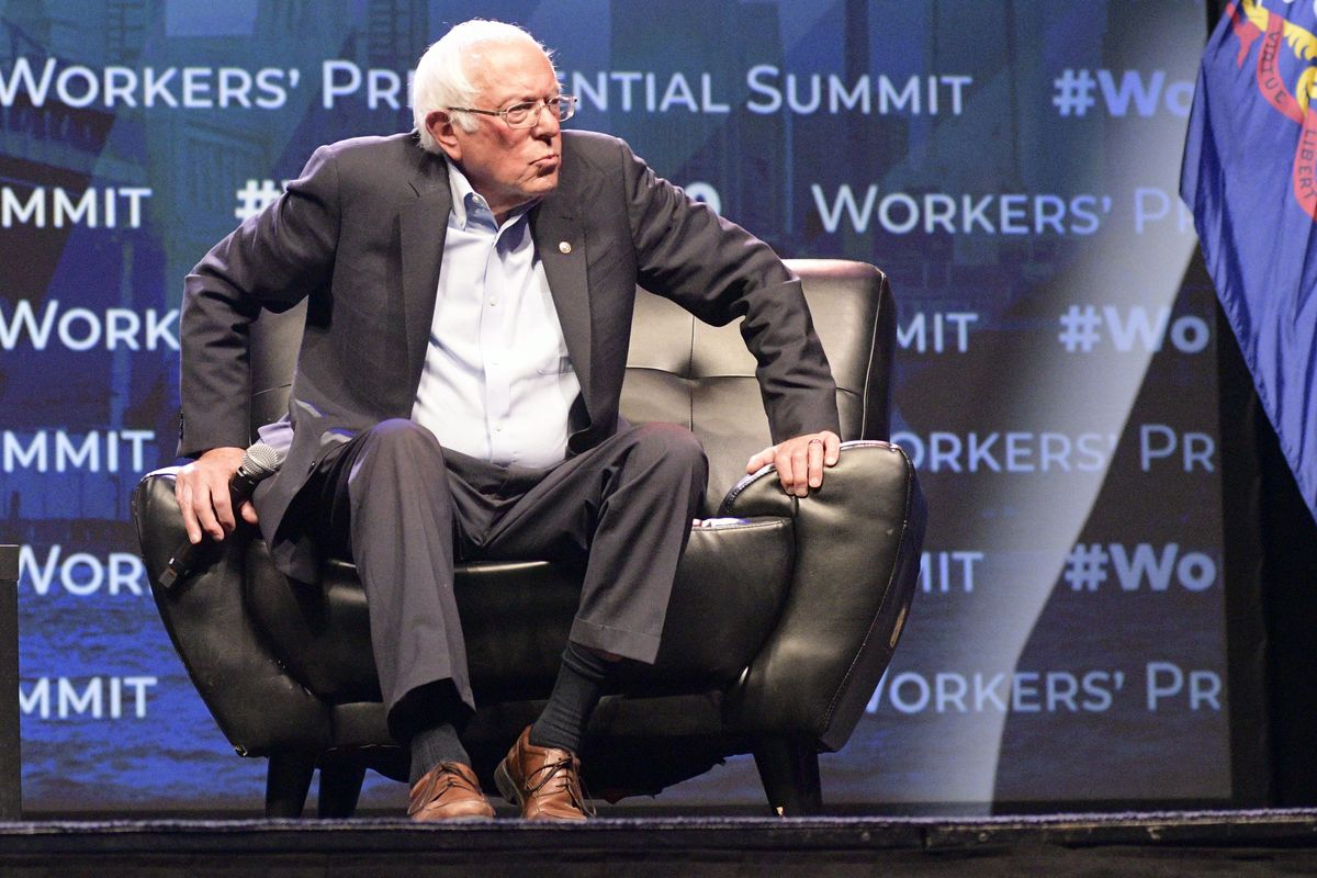Bernie Sanders lifts himself out of a chair onstage at the Workers' Presidential Summit in Philadelphia.