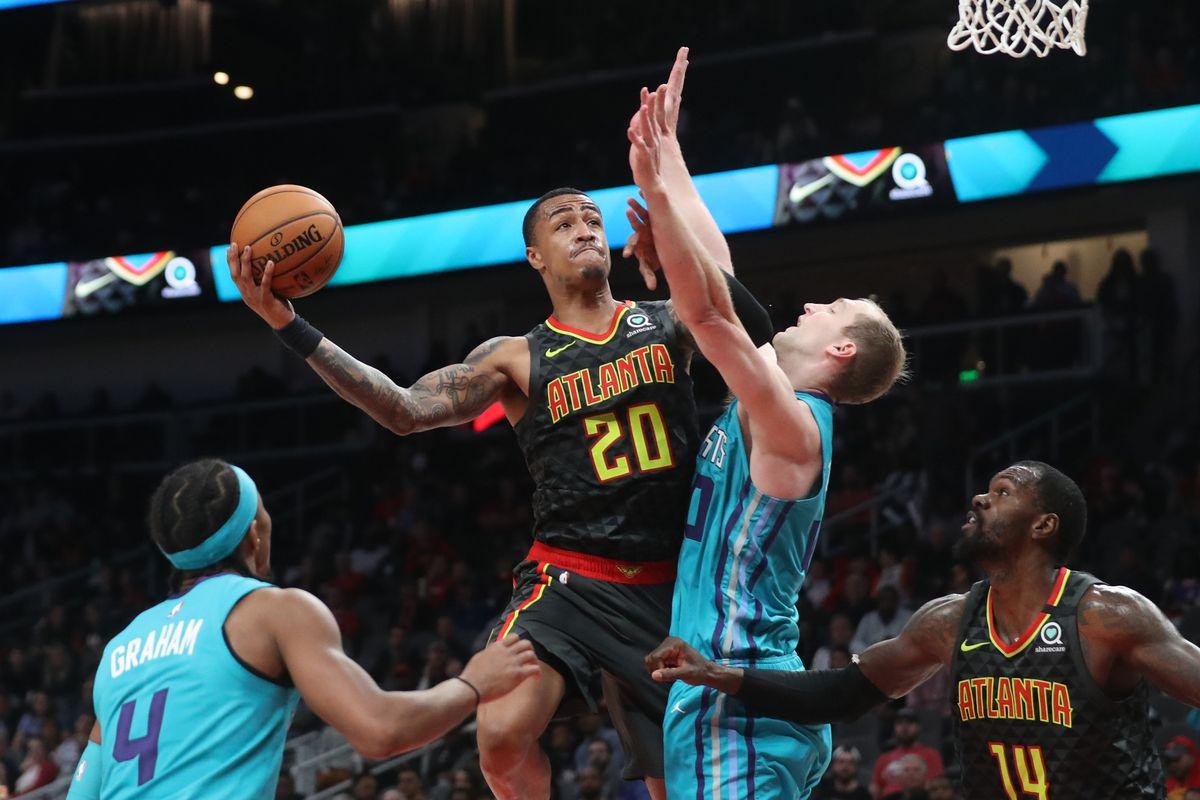 Atlanta Hawks forward John Collins (20) attempts a shot against Charlotte Hornets center Cody Zeller (40) in the fourth quarter at State Farm Arena.