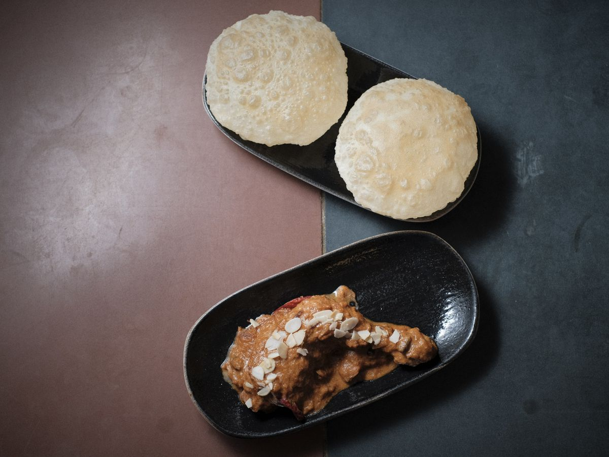 Puri at Darjeeling Express, on a black platter and a pink and navy background