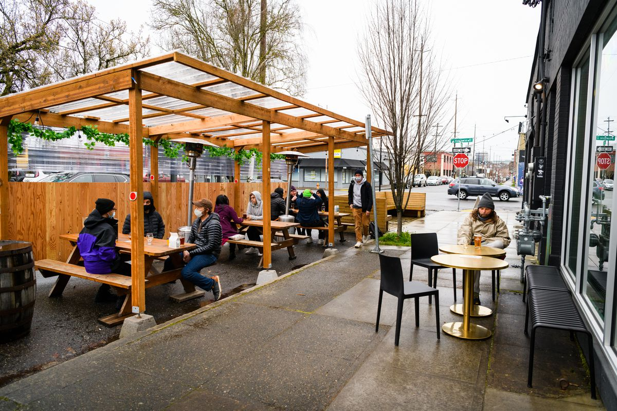 The outdoor patio outside the brewery Away Days is covered with a wooden awning.