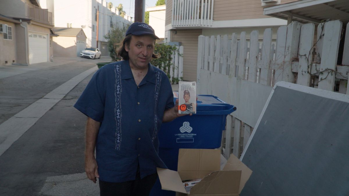 Gregg Turkington holds up a copy of Breakfast at Tiffany's near a set of garbage cans