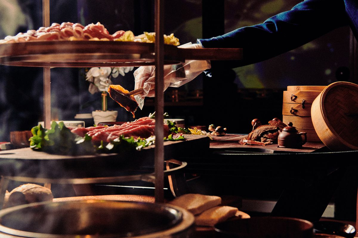 A multi-tiered platter of raw meat stands in the immediate foreground, while a server behind it prepares other meats tableside
